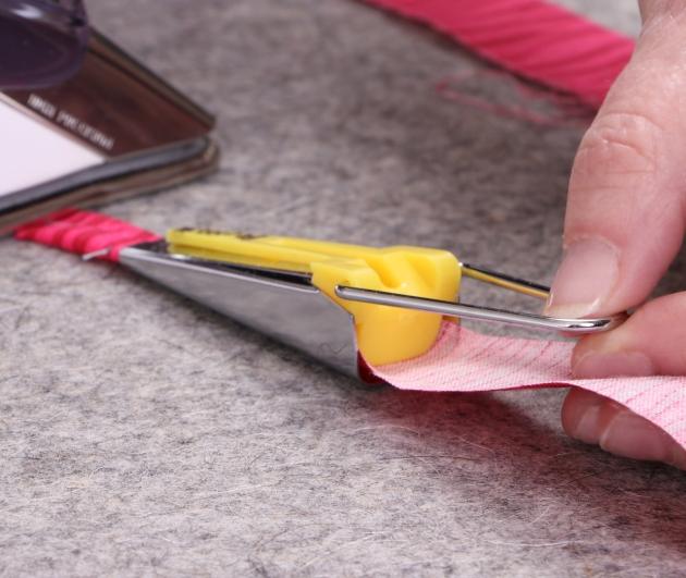ironing bias tape as it feeds through maker